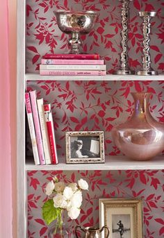 Pretty in pink. This bookcase has a glamorous feel, with it's patterned paper background, fresh white flowers, shiny photo frames and vase along with books of similar colours.