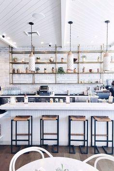 Open shelving, modern pendant lights and classic subway tile backsplash in an open plan kitchen.