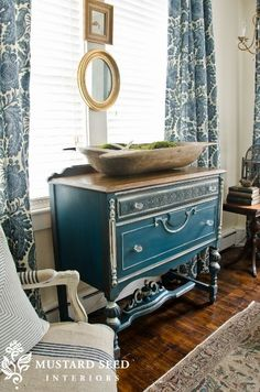 I LOVE the blue chest of drawers. The wooden dough bowl and printed curtains are pretty awesome as well.