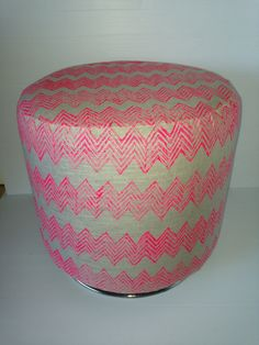 Gorgeous hot pink handprinted linen chevron round ottoman. This ottoman has a wooden frame (max weight 100kgs) and is perfect for an extra seat in a children's room or nursery, a foot rest or even a side table! This ottoman swivels, providing hours of fun for kids and adults alike and can be used for years and years.     Please contact me for courier costs.     This ottoman measures 45cm x 46cm x 46cm.
