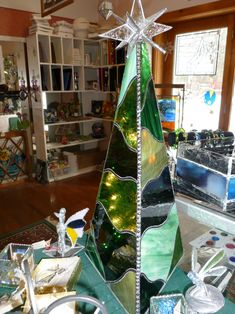 Three sided 3D stained glass Christmas tree with a variety of shades of green.  Lighted from within with a string of sparkling Christmas lights.  This table top tree will adorn any home with the warmth of the Christmas holiday.