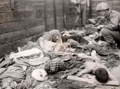 Dachau, Germany, May 1945, American soldiers aboard a boxcar, laden with corpses.