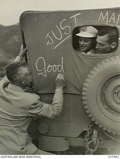 Nadzab, New Guinea. 23 August 1944. Lieutenant Colonel Charles Mayo writing good wishes on the back of a jeep after the wedding ceremony at the hospital chapel. Just married, the bride Lieutenant (Lt) Myrtle R. Nuck, US Army Nursing Corps of Iowa, and groom Lt Herbert B. Jackman, US Airforce of Cleveland, Ohio, are looking through the back of the jeep.