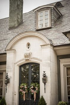 House façade exterior, double arched glass and wrought iron doors, smooth masonary.