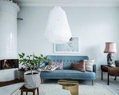 Blå soffa och vit taklampa. Rosa detaljer och grön växt.