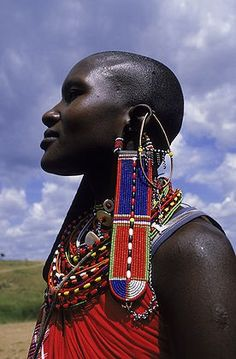Africa | Art work and decorations hang from the ears and neck of a Masai woman. Kenya |  © Jose Azel