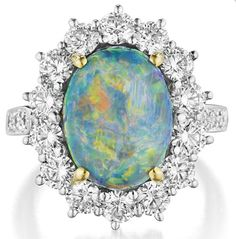 Tiffany & Co.  A Black Opal and Diamond Ring.   Set to the center with a cabochon black opal, within a circular-cut diamond surround, to the circular-cut diamond half hoop, mounted in platinum and 18K white gold