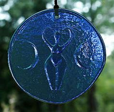 """Goddess Suncatcher - Blue - New Lower Price!Classic Goddess figure framed by two crescent moons. Made of blue glass. Approx. 4"""" in diameter. Comes with a hemp cord and glass beads for hanging."""