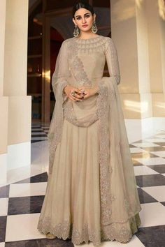 Exhibiting an elegant embroidery and stitch detailing, this dark beige dupion silk anarkali suit which will add oodles of charm to your special ethnic look. This round neck and full sleeve wedding wear dress highlighted with stone work and zari work. Available with santoon/ lycra churidar in dark beige color with dark beige net dupatta. Churidar is plain. Dupatta embroidered with stone and zari work. #anarkalisuit #usa #Indianwear #Indiandresses #andaazfashion Anarkali, Salwar Kameez, Sari, Embroidery, Suits, Stone, Brown, Women, Fashion