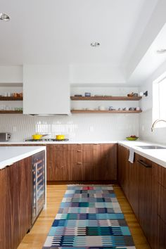 Gorgeous walnut kitchen design with midcentury modern feel - love the narrow rectangle tiles installed veritcally, the walnut open shelving, the solid white counters, the blue patterned runner, and the white boxy range hood cover - basically, everything. This is my dream kitchen right here...