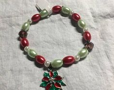 Check out Red green white Christmas poinsettia beaded stretch bracelet, Christmas jewelry, pearl bracelet, charm bracelet, gift for her, Handmade on dawnsbeadsdesigns