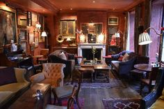 Warm, cozy knock-out of a room...check out the plank floor, the red walls, wall art, and seating that looks like it would just soak someone up.  This room is wonderful and would seat a LOT of people (The Zetter Townhouse bar). COZY