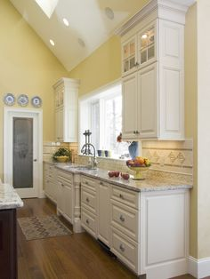 Kitchen design - pairing yellow walls with marble countertops and hardwood flooring
