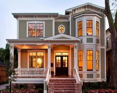 traditional exterior by Whitestone Builders; with a two-story bay window and the coordinating gable roof