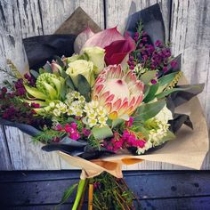 Inspiration for wedding flowers: Something really wild using Protea in the center.  This bouquet is my inspiration for all flowers- but altered a bit with available flowers.  (Note: if florist doesn't have Protea I will use fake Protea flowers surrounded by real flowers that are available.)