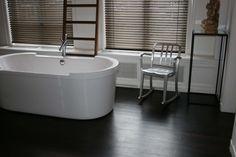 Een houten vloer in de badkamer? Ook dat is mogelijk! Hier een prachtige Wengé strokenvloer. Hardhout wat met de juiste afwerking goed waterbestendig is.