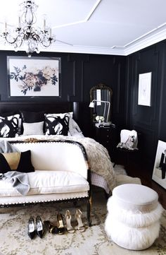 Glam bedroom with bold black walls, a crystal chandelier and fur accents