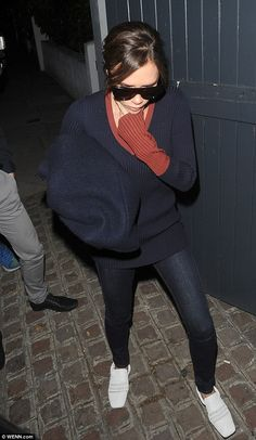 In the navy: She talso donned with a baggy V-necked navy sweater and matching skinny jeans...