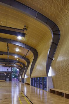 Acoustic panels line the huge expanse of the ceiling and at the southern end sweep in a curve down the wall in the interior of the multi-purpose sports hall at Abbotsleigh School for Girls. Photos by Tyrone Branigan