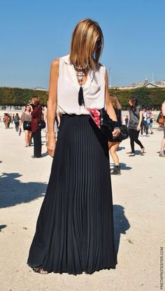 black pleated maxi skirt with white blouse and tassel necklace