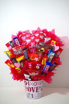 A handmade arrangement of your favorite candy in a white love tin. A great gift for Valentine's Day . Arrangement contains a mix of candy including Kit Kat, Skittles, Twix, Variety of M&Ms, Almond Joy