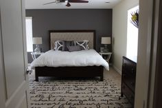 Modern master bedroom featuring Stanley furniture bed and dresser, tables and area rug from West Elm and bedding from Eastern Accents.