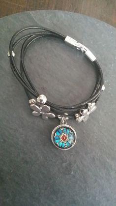 Zwart leren armband metalen bloemen en kralen en prachtige verwisselbare glashanger.