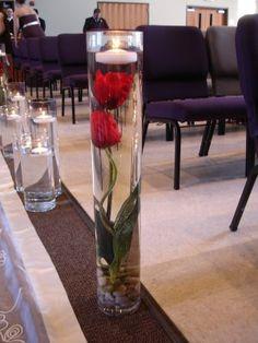Cilindros con agua, piedras, flores y velas