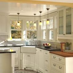 Corner Farmhouse Sink ; Island ; Varying counter height to accent butcher block ; Light pattern ; overall layout