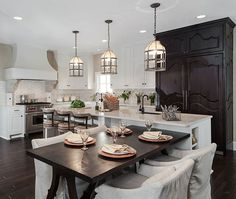 Here's a final exercise in contrast: white island with matching countertop holds attached dark wood dining table in large, open kitchen with imposing dark wood cabinet and matching hardwood flooring.