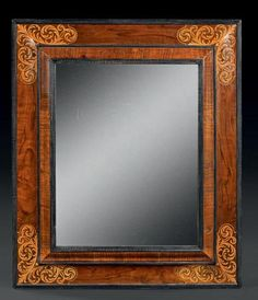 Miroir en bois de placage à décor marqueté d'écoinçons de bois clair.