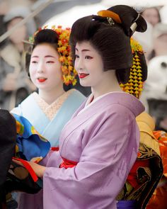 Satsuki makes a public appearance accompanied by a maiko and a minarai, possibly her younger sisters, who benefit from basking in the glow of her fame.