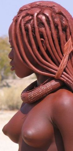The Himba wear little clothing, but the women are famous for covering themselves with otjize, a mixture of butter fat and ochre. The mixture gives their skins a reddish tinge. This symbolizes earth's rich red color and the blood that symbolizes life, and is consistent with the Himba ideal of beauty.