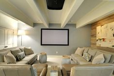 Even a small basement can be put to good use. Fill it up with cozy furniture and soft colors, as in this room, and you have a dedicated movie-watching space. The wood wall adds a subtle architectural element.