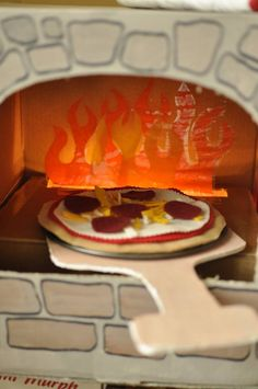 DIY cardboard pizza oven with laminated tissue flames and DIY felt pizza. String lights light the flame!