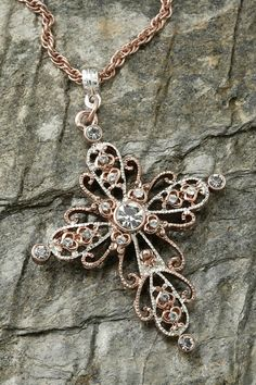 "Richly adorned with sparkling crystals and charming heart designs in the center of this cross make this pendant one that you can wear with just about anything. - 30"" Rose gold-tone chain - Pendant mea"