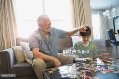 Stock Photo : Playful grandfather and grandson solving puzzle at home