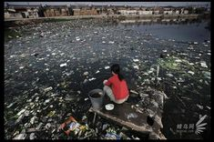 Guiyu, Guangdong province, (广东省贵屿镇) rivers and reservoirs have been contaminated, the villager is washing in a seriously polluted pond. November 25, 2005