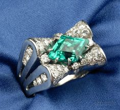 Platinum, Emerald and Diamond Ring, c. 1935, prong-set with a navette shape faceted emerald weighing approx. 2.20 cts., bow form mount and split shoulders set with diamond melee