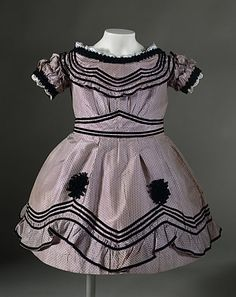 Child's dotted print dress with black trim, English, 1864.