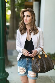 White jacket, black t-shirt, distressed denim shorts, Louis Vuitton Speedy bag.