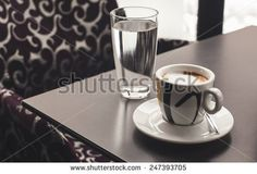 Cup of coffee and glass of water on table in a cafe.