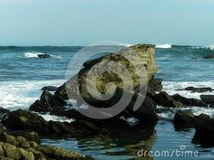 A view of large granite fish-shaped rock with crashing waves at an eastern cape beach in South Africa.