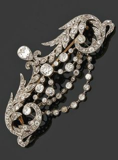 A diamond, platinum and gold 'stomacher' brooch, circa 1890-1900. In the garland style composed of two large foliated arabesque, suspending three wreaths in between, set throughout with diamonds, mounted in platinum and gold.