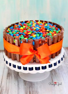 How to Make a Kit Kat Cake recipe- Kit Kat candy bars surrounding a chocolate frosted chocolate cake with M&M's filled in on top! - So easy to do, and such an impressive cake for festive occasions.