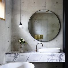 Minimalist inspired bathroom with concrete walls, and a marble sink