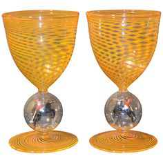 A Pair of Art Glass Bimini Stem Goblets With Polo Figures  Austria  1920-1935  The stems have intricate and marvelous coloured swirl glass with a fantastic hollow bubble containing an animal. Both glasses are in yellow with a polo player in the bubble.