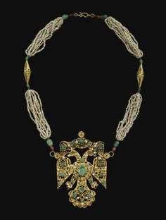 A GEM-SET GOLD DOUBLE-HEADED EAGLE PENDANT, MOROCCO, 18TH CENTURY the large central pendant featuring a double-headed eagle worked in filigree and set with emeralds, pearls and red gemstones, the necklace composed of two clusters of pearls on each side of hook, separated by a gold conical filigree bead