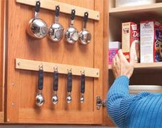 measuring cups & spoons hanging in cabinet