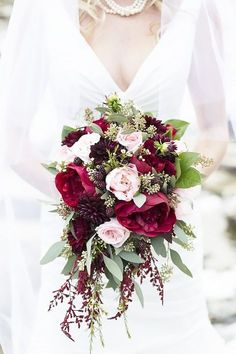 We love everything about this mysterious, alluring bouquet that features pink and deep red peonies, merlot dahlias, and plump blackberries. It's a good idea to have some flexibility when it comes to the flowers. Think of your florist like you would a chef: They go to the market and select the best flowers available, so if the big day comes and dahlias are prettier than ranunculus, you might have to have a bouquet of peonies and dahlias instead of peonies and ranunculus. 12 Stunning Wedding…